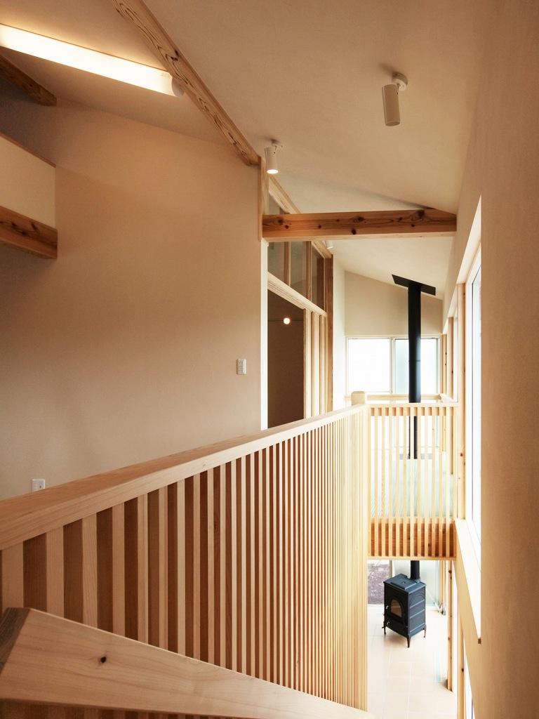 1階と2階をつなぐ階段の先に見える薪ストーブ