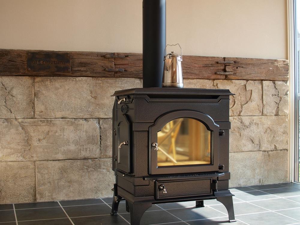 薪ストーブの背面はモルタル造形。この家のテーマ、「Natural Life Style」を刻印