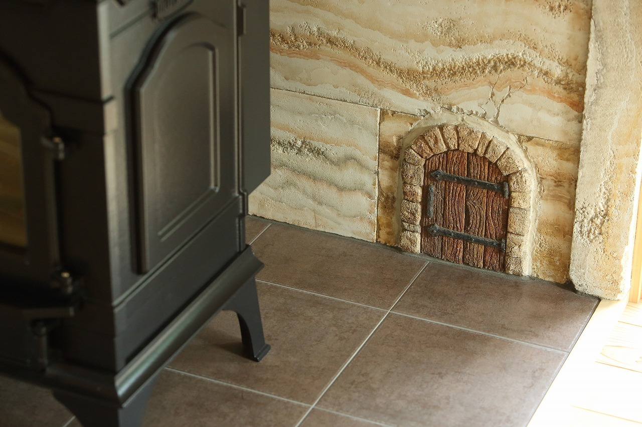 薪ストーブの後ろには、トラバーチンのモルタル造形。おや?小さなドアが…?