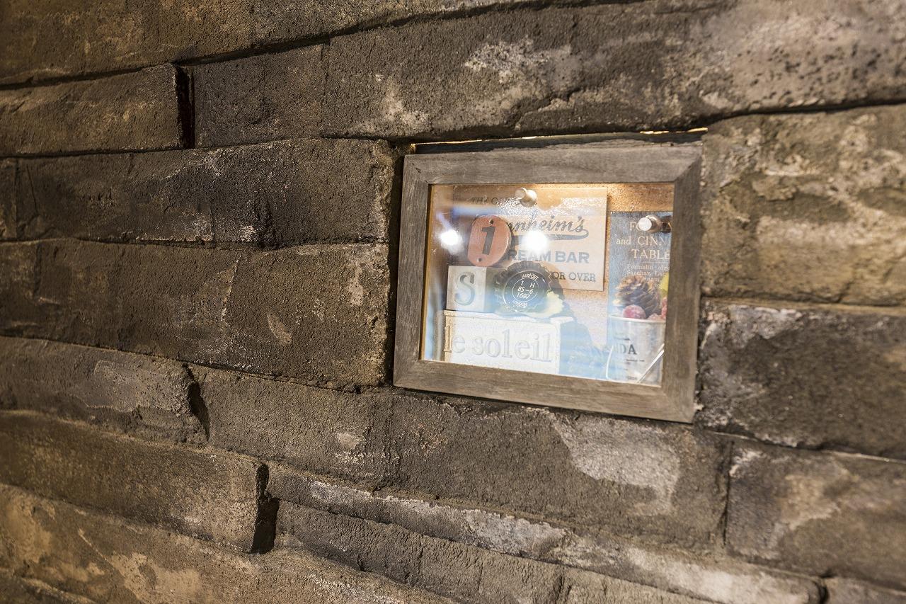 ホールにはモルタル造形で割石積みを再現し、照明付きのニッチにはお気に入りの小物が