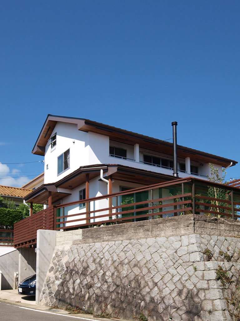 高台に建つ漆喰の家
