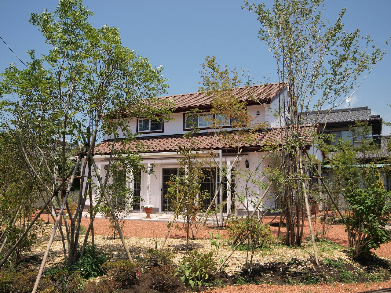 雑木林をイメージしたお庭。漆喰の白い壁と素焼きの洋瓦とのコントラストが素敵です。
