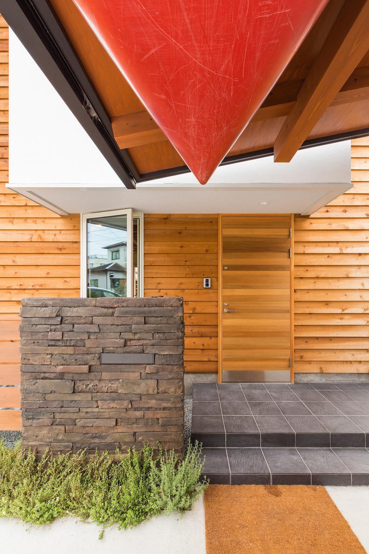 腐りにくいウエスタンレッドシーダーの外壁と玄関戸の前には、モルタル造形の門柱