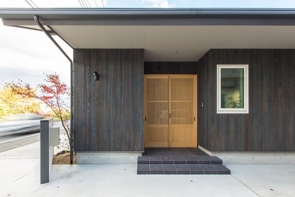 外壁と玄関建具は既製品にはない暖かさがある。