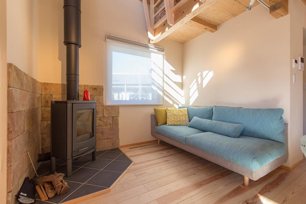 リビングの薪ストーブスペース。素敵なソファーとモルタル造形。