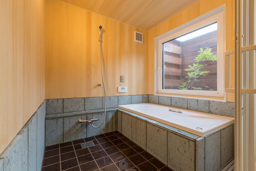 ヒバの薫る浴室。腰壁は濡れると緑色に美しく変わる十和田石で、床は暖かく柔らかいコルクタイル。