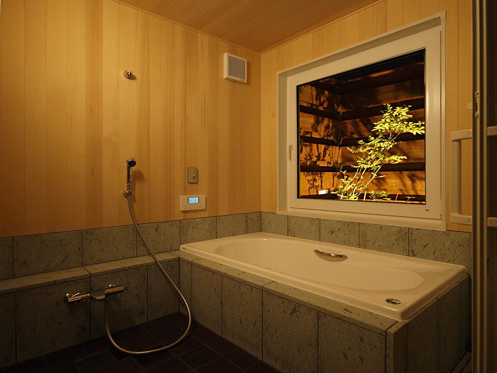 夜は大開口サッシに面した坪庭の明かりをつけて、ゆったりくつろげるオーダーメードの浴室。
