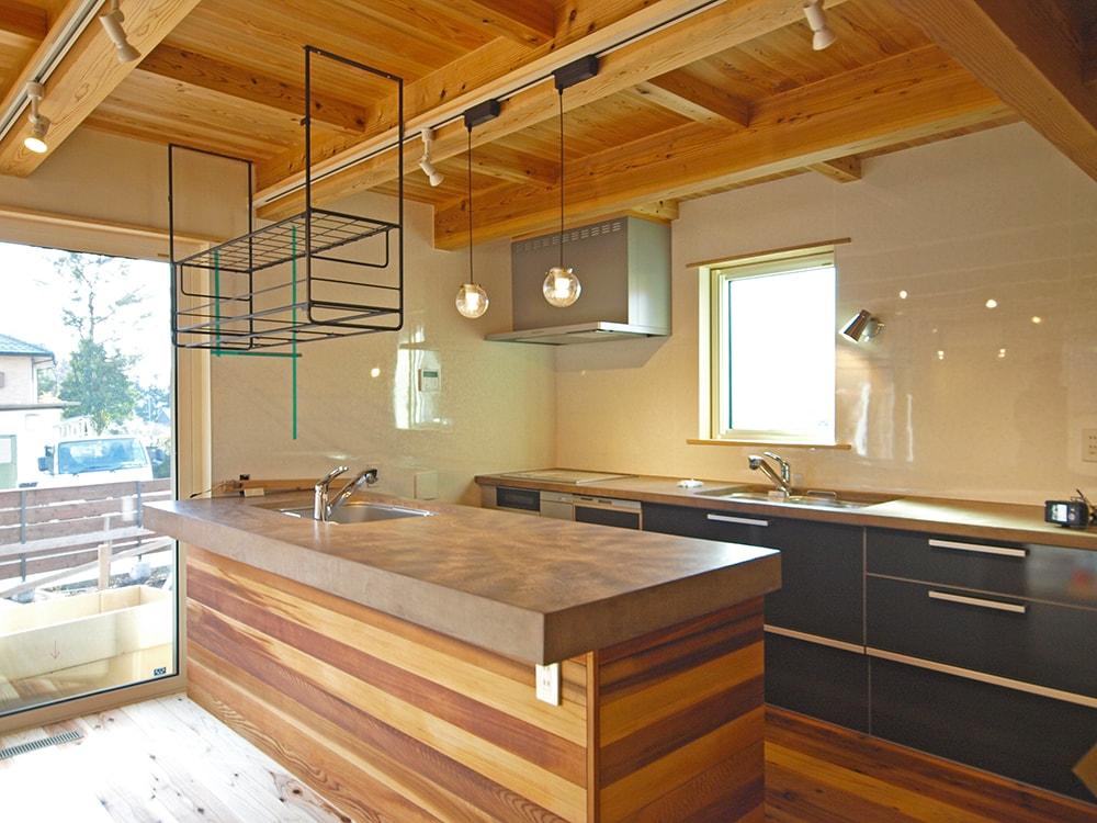 室内のキッチンは、LIXIL軒製品のキッチンと、大工が作ってモールテックスで仕上げたオリジナル天板を組み合わせ。