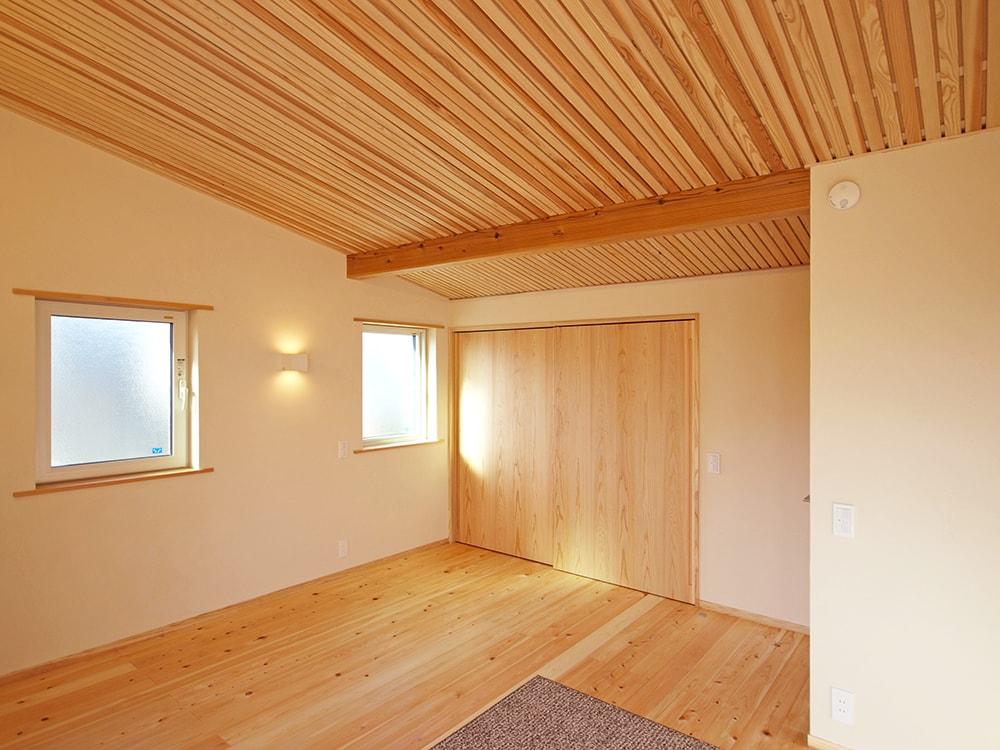 二階寝室は、壁を調湿性抜群の湯布珪藻土、天井は杉の格子仕上げとして、格子の上の木質繊維断熱材の調湿性を発揮できるようにした。
