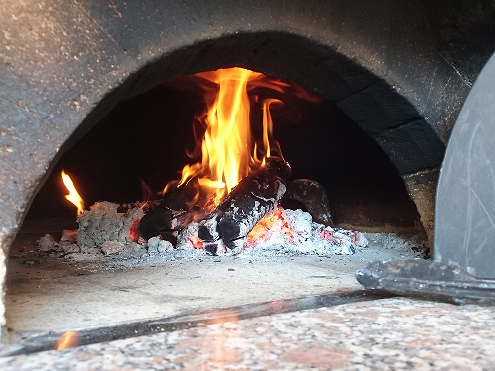 数時間とろ火で燃やし続けることで、連続して何枚もピザが焼ける。