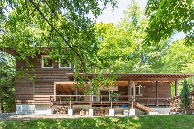 森の中の斜面に立つ自然素材の家。木の外壁は、経年変化と共にこの自然に溶け込んでゆく。