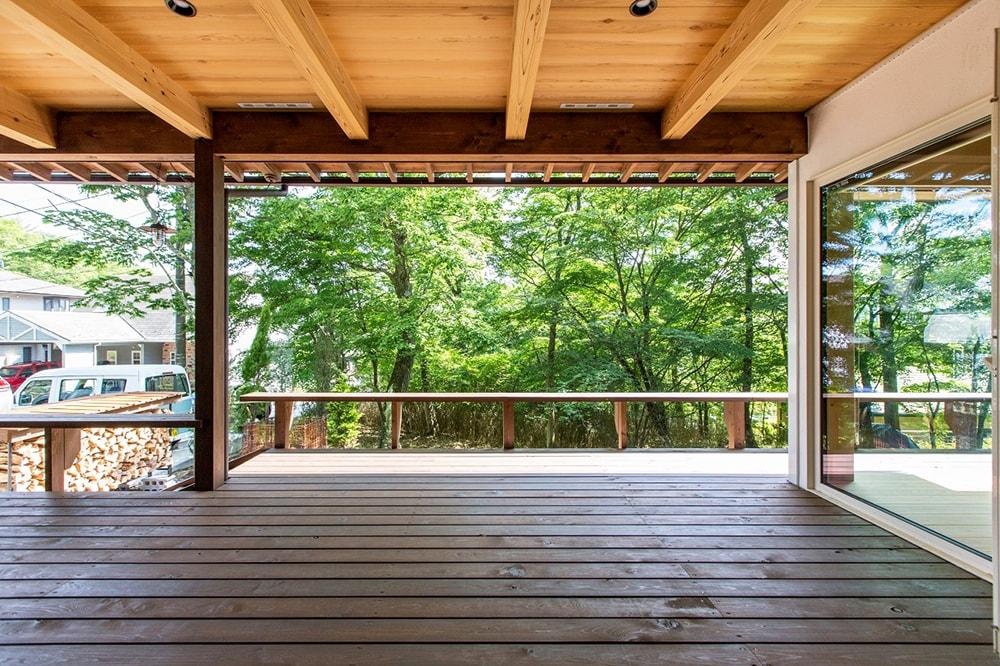 玄関を入ると、目の前に屋根のかかった広いデッキに繋がり、自然が飛び込んでくる。