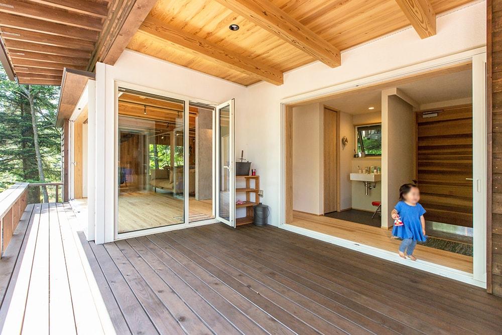 広いウッドデッキは寝室と廊下とリビングを一つにつなぐ。