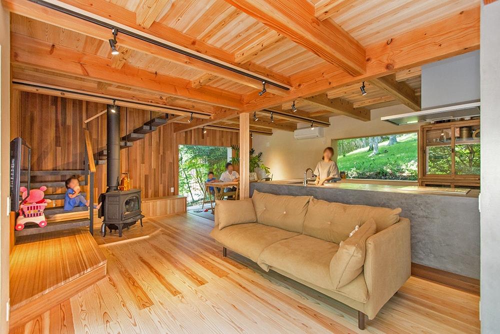 リビングにはヨツールの薪ストーブと、モールテックスの造作キッチンを配置。どの方向も緑に向かって開いている。