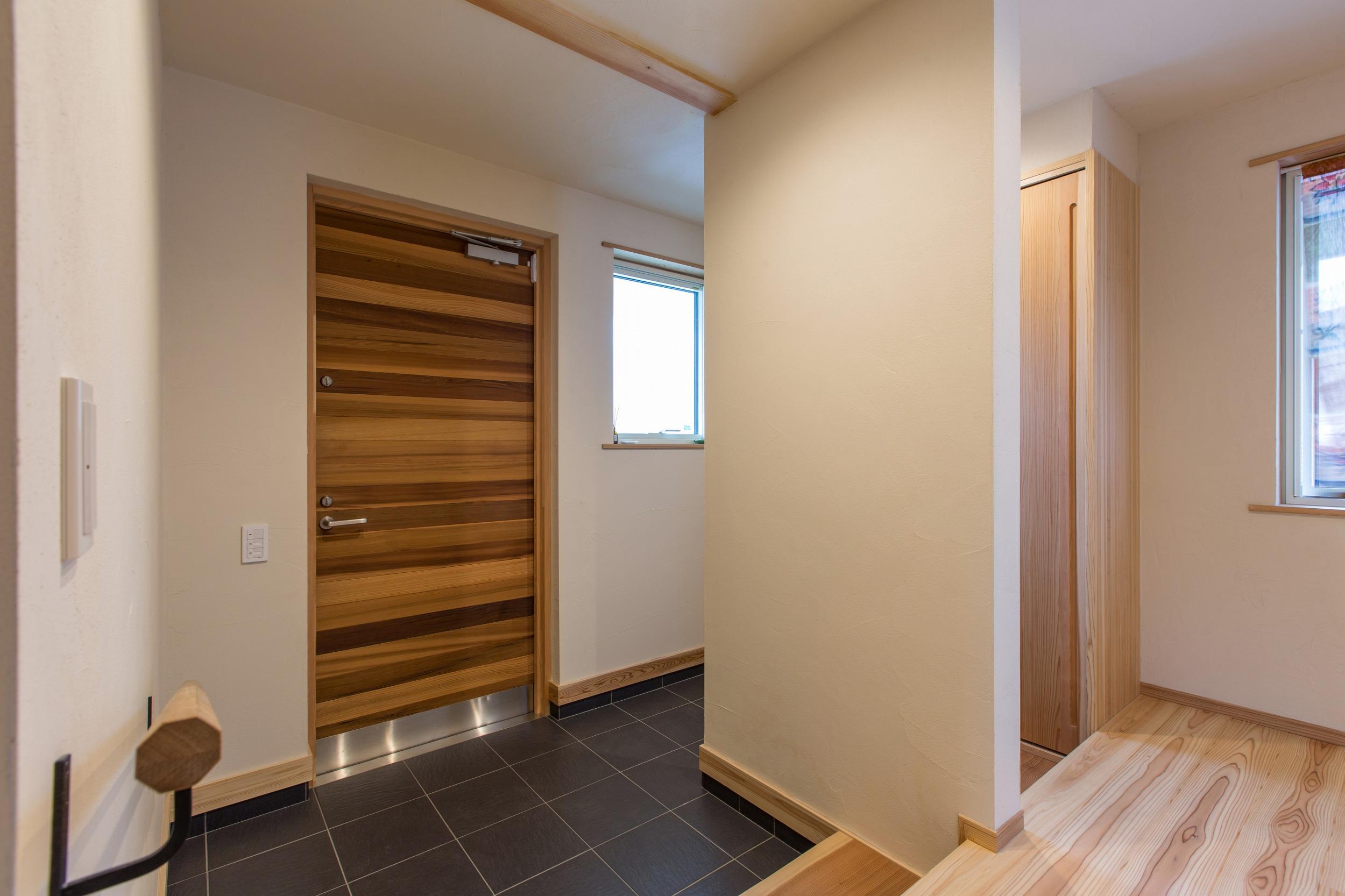 レッドシダーの戸から入ると、シューズクローク併設した玄関。敷台は解体前の家のカウンター。