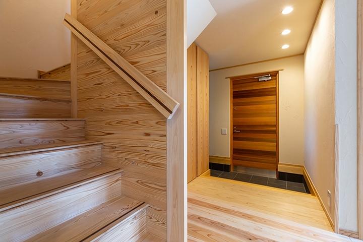 木の玄関を入ると、湯布珪藻土と杉の床の自然素材の空間。奥はシューズクローク。