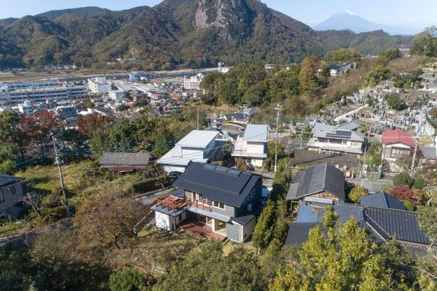 たくさんの木々と山々に囲まれた自然豊かな土地に建つ。晴れた日には二階のデッキから富士山も眺めることができる。