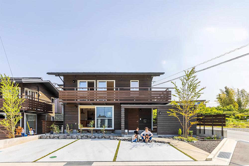 分譲地の角に立つ本物の木の外観は、住まい手だけでなく、街角にも優しい家。